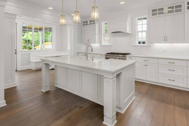 vackert vitt kök i nya lyxhus med ö, pendel ljus och trä golv. funktioner rost fritt stål apparater och bondgård stil sjunka - looking inside inside cabinet bildbanksfoton och bilder
