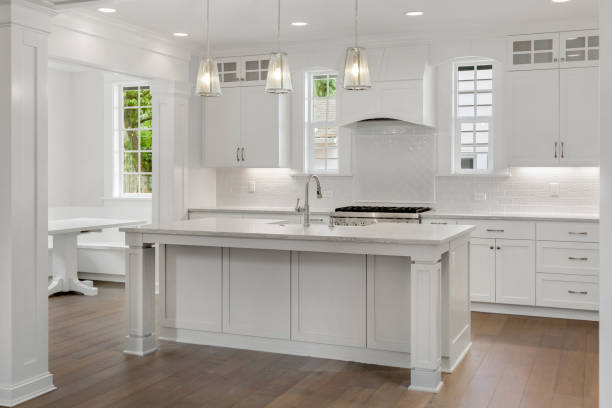 beautiful white kitchen in new luxury home with island, pendant lights, and hardwood floors. Features stainless steel appliances and farmhouse style sink stock photo