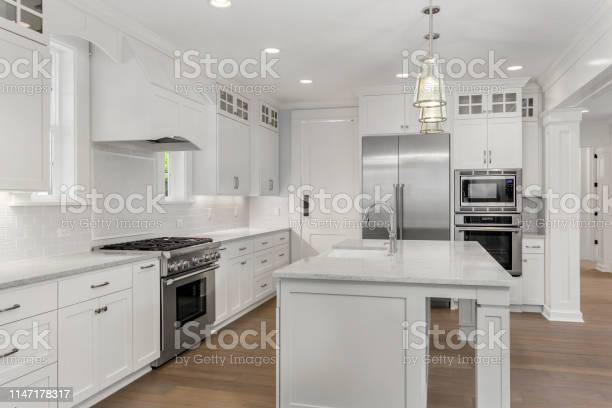 Beautiful white kitchen in new luxury home with island pendant lights picture id1147178317?b=1&k=6&m=1147178317&s=612x612&h=ejf 0cgvm6bg404opzpqybdaqelfsee3l2wyrsqda90=