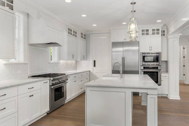 beautiful white kitchen in new luxury home with island, pendant lights, and hardwood floors. features stainless steel appliances and farmhouse style sink - kitchen situations foto e immagini stock