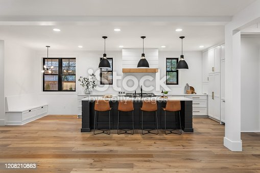 676153162 istock photo beautiful white kitchen in new luxury home with island, pendant lights, and hardwood floors. Island and Counters are Black, Hardwood Floors are Dark, and Cabinets, Backsplash, and Woodwork are White 1208210863