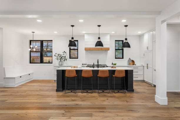beautiful white kitchen in new luxury home with island, pendant lights, and hardwood floors. Island and Counters are Black, Hardwood Floors are Dark, and Cabinets, Backsplash, and Woodwork are White