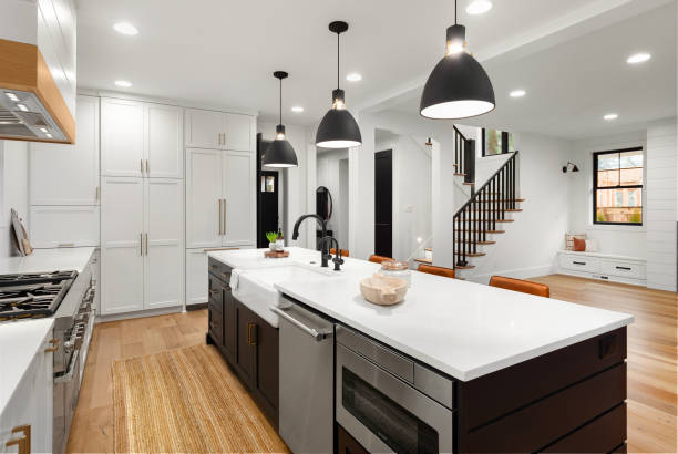 Beautiful white kitchen with dark accents in new farmhouse style luxury home