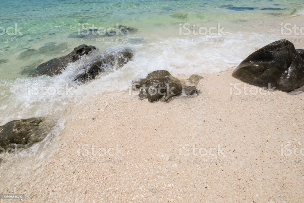 beautiful white sand beach with soft ocean wave and rocks in summer time, wave of the blue sea on the sand bech. concept travel. stock photo