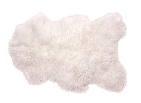 Beautiful white sheepskin isolated on white background. Warm carpet.