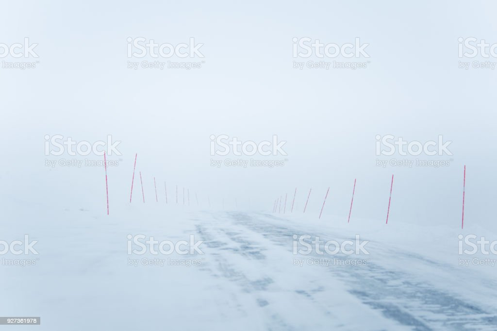 A beautiful white snowy road in central Norway with a red safety poles. A beautiful white snowy road in central Norway with a red safety poles. Minimalist winter scenery un northern Europe. Agricultural Field Stock Photo