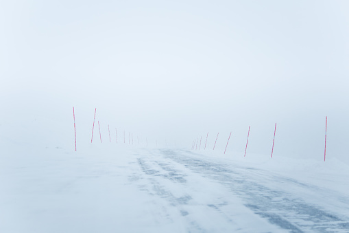A Beautiful White Snowy Road In Central Norway With A Red Safety Poles Stock Photo - Download Image Now