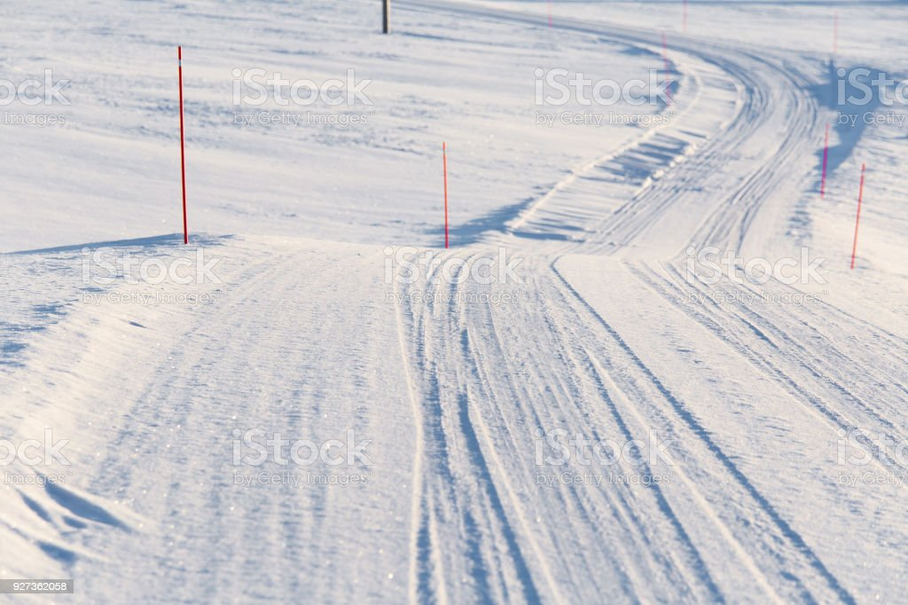 A beautiful white snowy road in central Norway with a red safety poles. - Royalty-free Agricultural Field Stock Photo