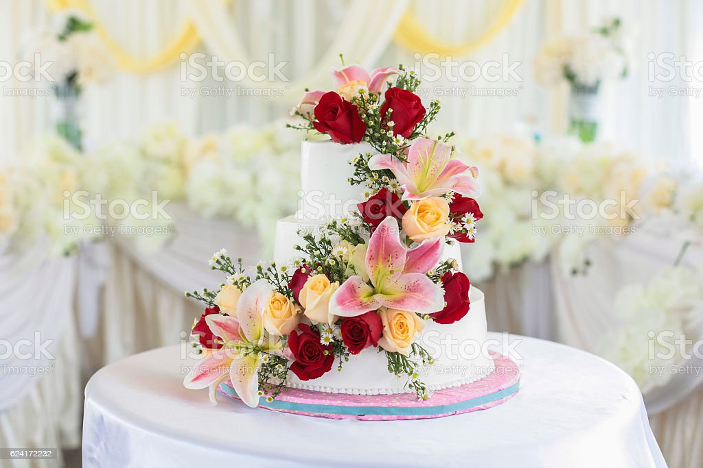Beautiful white wedding cake with red roses as decoration. – Foto