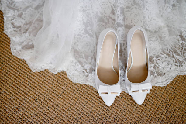 Beautiful white wedding dress and shoes for bride indoors stock photo