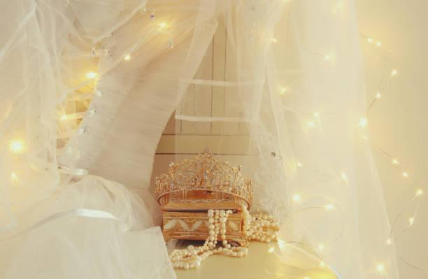 schöne weiße hochzeitskleid und schleier auf stuhl mit gold girlande lichter - prinzessin tiara stock-fotos und bilder