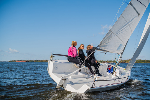 A beautiful white yacht is sailing in the wind on the river against the background of a beautiful autumn forest. A guy on board with two girls