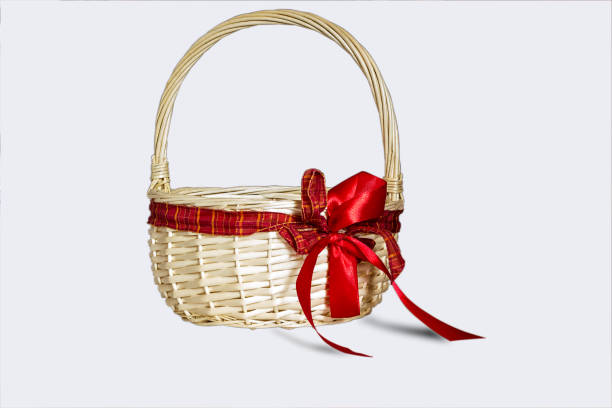Beautiful wicker basket with red bow isolated on white background stock photo