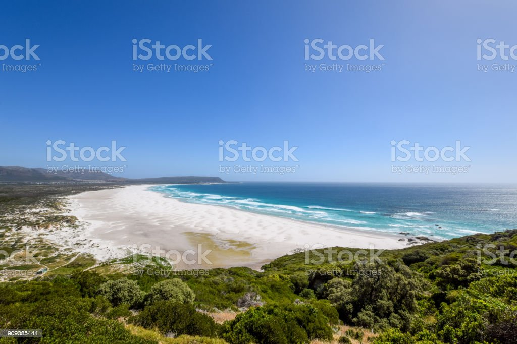 Beautiful wide angle panoramic view of Noordhoek Long Beach near Cape Town, South Africa. The town of Kommetjie with its beautiful lighthouse is located at the back end of the beach. stock photo