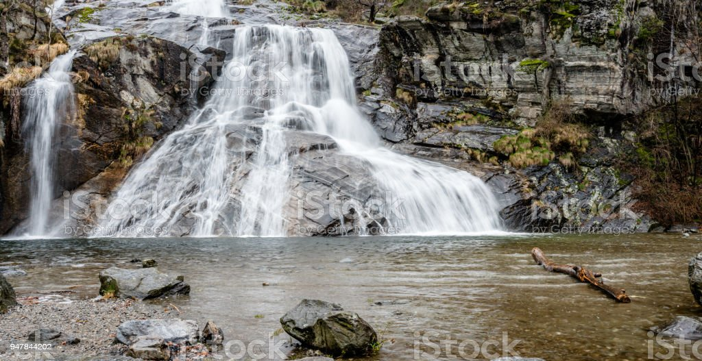 beautiful wide waterfall with a swimming hole in the foreground in the early morning in southern Switzerland stock photo