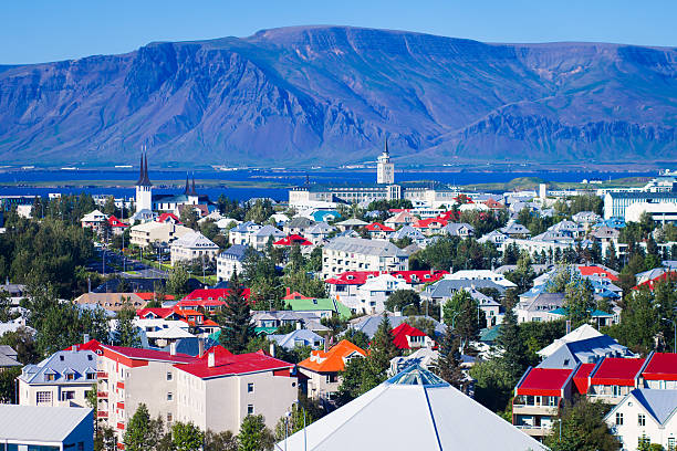 Beautiful wide-angle aerial view of Reykjavik, Iceland harbor and skyline Beautiful summer super wide-angle aerial view of Reykjavik, Iceland with harbor and skyline mountains and scenery beyond the city, seen from the observation tower of hallgrimskirkja church with blue sky in sunny day. auk stock pictures, royalty-free photos & images