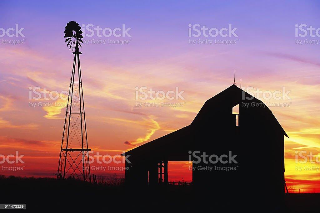 Beautiful windmill and barn at sunset stock photo