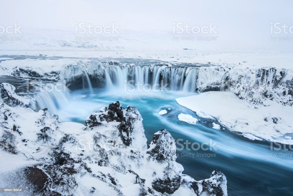 Beautiful winter Godafoss waterfall in Iceland, covered in snow, stock photo