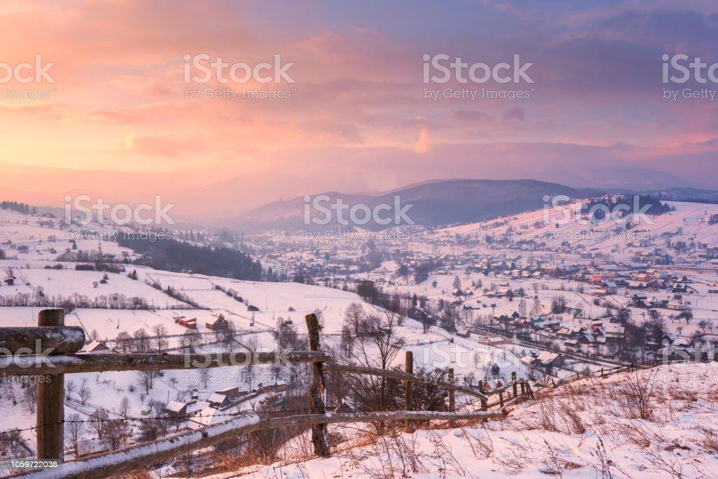 Herrliche Winterlandschaft in weichen Sonnenuntergang leichte, alpine Tal, umgeben von bewaldeten Bergen – Foto