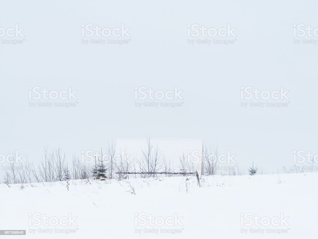 Beautiful winter landscape, small cottage during a snowfall, field. Winter fairy tale, solitude in the snows stock photo
