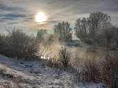 Beautiful winter landscape. White snow-covered trees and shrubs on the river Bank with fog and steam.Russia  .The photo was taken on a mobile phone