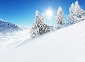 Beautiful winter landscape with ideal piste. Blue sky with sun light and high Alpine mountains on background