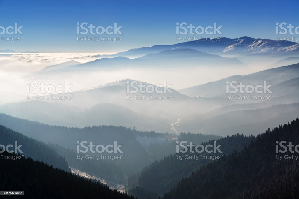 Beautiful winter landscape with morning fog in the mountains stock photo