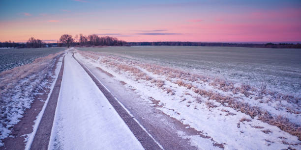 A beautiful winter morning landscape with a gravel road. Bright, extra colorful scenery of Northern Europe. stock photo