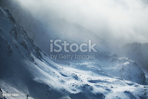 Aerial view of snowy mountains at winter day. Stormy weather, Canillo ski region, Andorra