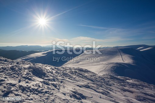 Beautiful winter panorama with fresh powder snow. Landscape with spruce trees, blue sky with sun light and high Carpathian mountains on background