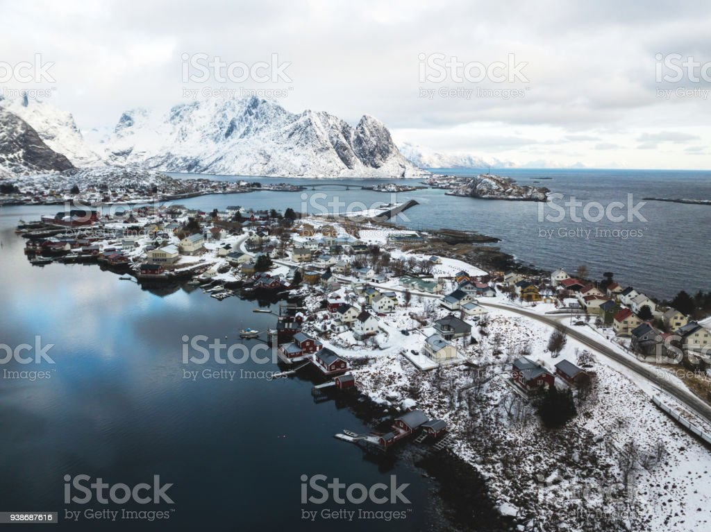 Beautiful winter snowy wide-angle summer aerial view of Reine, Norway, Lofoten Islands, with skyline, mountains, famous fishing village with red fishing cabins, Moskenesoya, Nordland, shot from drone stock photo