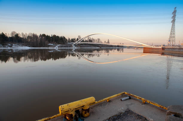 A beautiful winter sunrise at the residential district of Sompasaari, Helsinki. An arch bridge connecting the area to the Mustikkamaa leisure park. stock photo
