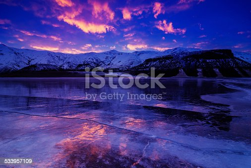 Beautiful winter sunrise with colorful clouds reflecting in frozen lake near Boise, Idaho, USA. This is Lucky Peak reservoir near Boise