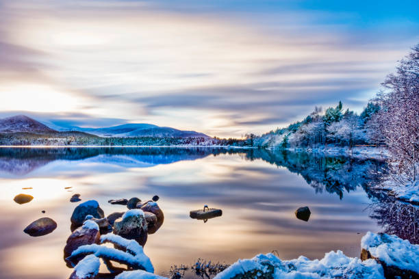 Beautiful winters day with soft clouds, snow on trees and rocks, reflections on calm water at Loch Morlich, Aviemore Beautiful winters day with soft clouds, snow on trees and rocks, reflections on calm water at Loch Morlich, Aviemore scottish highlands stock pictures, royalty-free photos & images