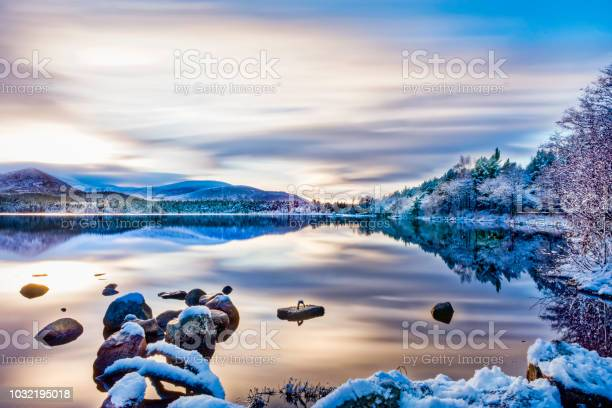 Photo of Beautiful winters day with soft clouds, snow on trees and rocks, reflections on calm water at Loch Morlich, Aviemore