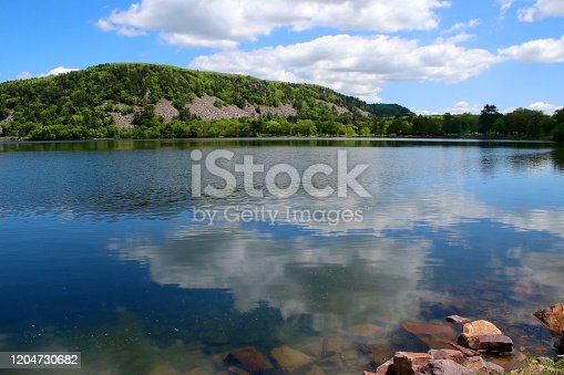 Devil's Lake State Park landscape with view on the East Bluff hiking trail hill behind a lake water with cloudy blue sky reflection. Baraboo area, Wisconsin, Midwest USA.