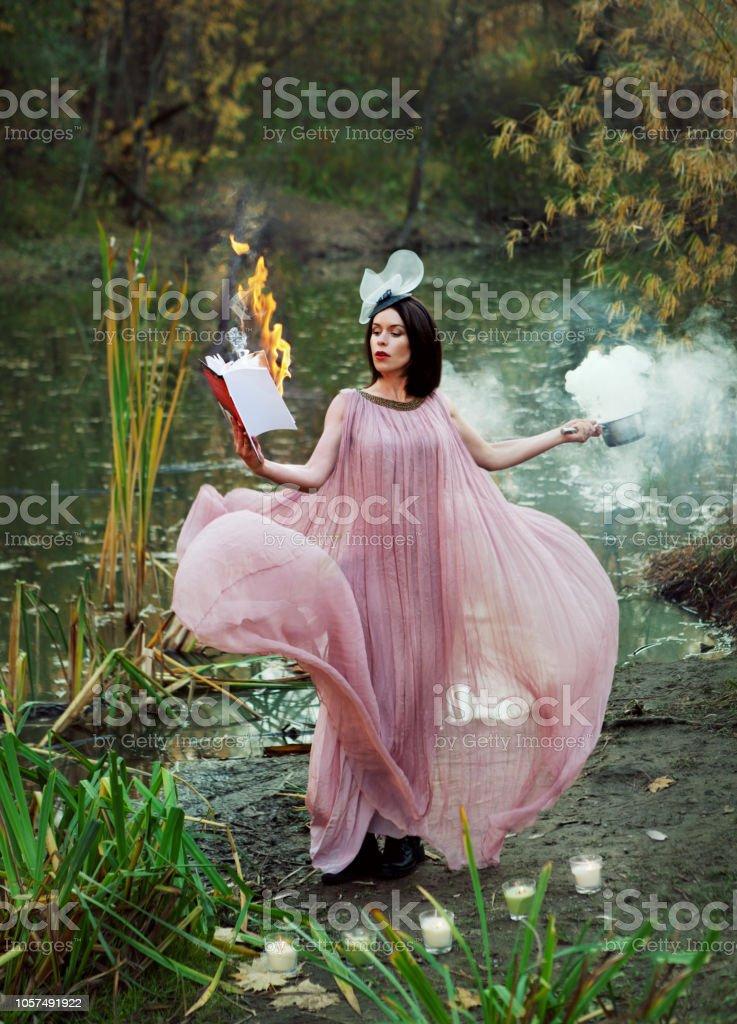 Hermosa bruja en el pantano mantiene un libro quemado y una poción mágica - foto de stock