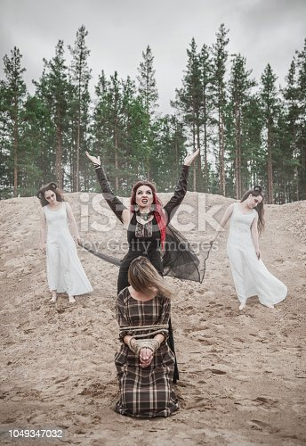 Beautiful witch with red hair and horned demons outdoor
