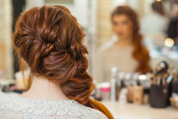Beautiful, with long, red-haired hairy girl, hairdresser weaves a French braid stock photo