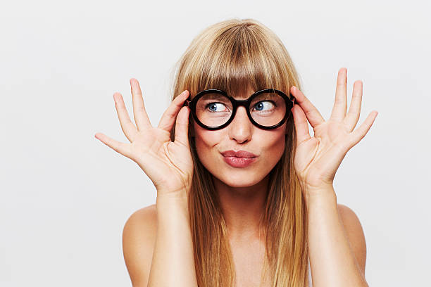 beautiful woman adjusting spectacles in studio - eyewear stock pictures, royalty-free photos & images