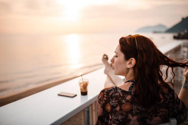 Beautiful woman admiring sunset above Ionian sea stock photo