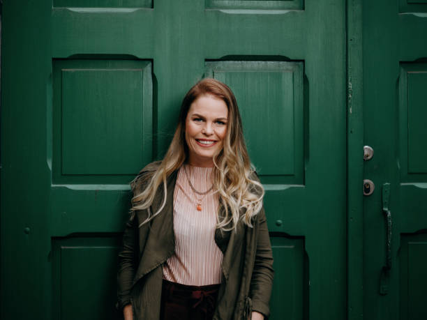 Beautiful woman agains green door stock photo