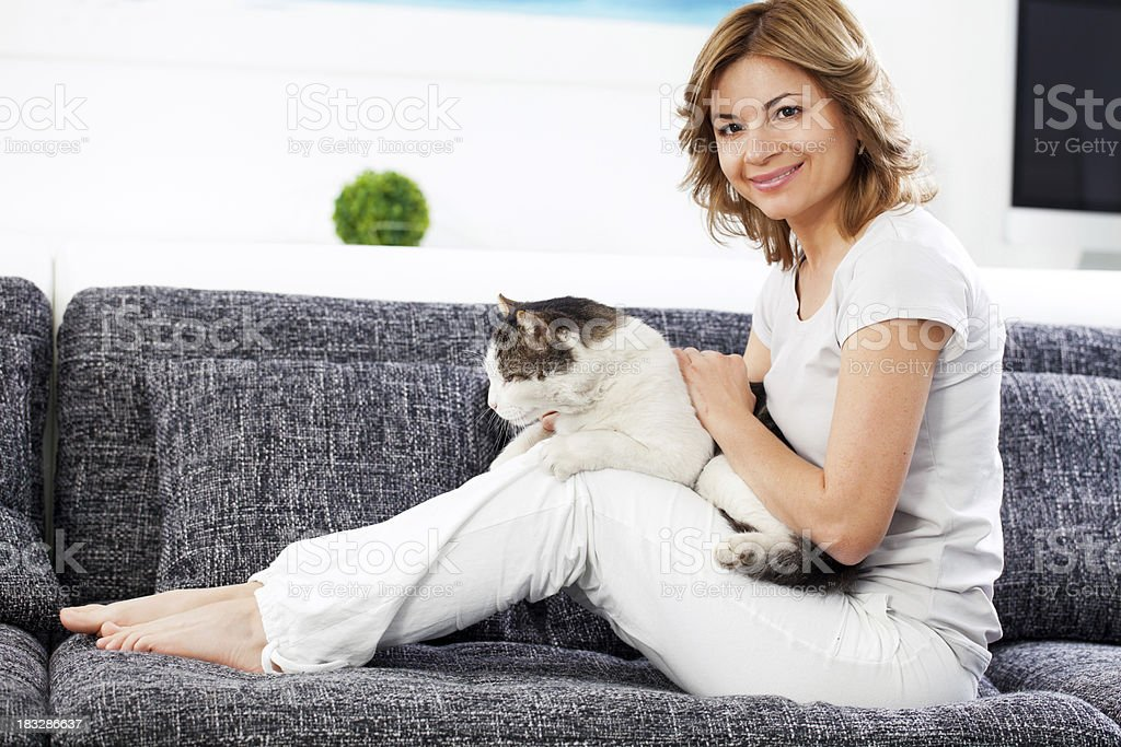 \'Smiling woman resting with pet, holding cat in arms and looking at...