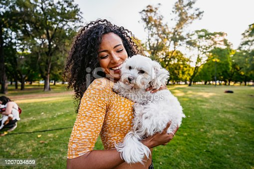 istock Beautiful woman and her dog in park 1207034859