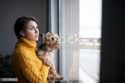 Beautiful Latino woman holding her dog and they looking through window.
