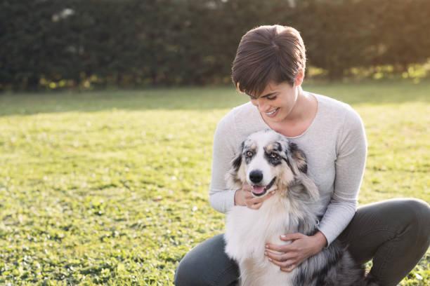 Schöne Frau und ihr Hund gemeinsam posieren – Foto
