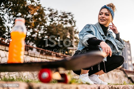 Young beautiful woman and juice bottle on skateboard.