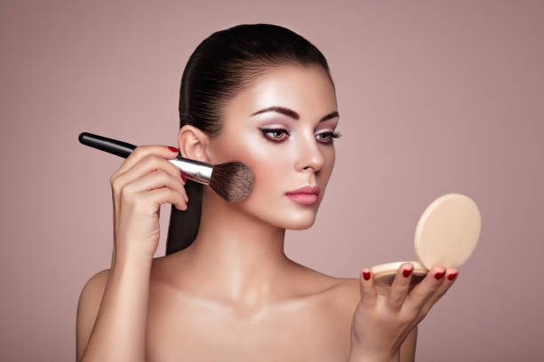beautiful woman applies skin tone with brush - make up stock photos and pictures