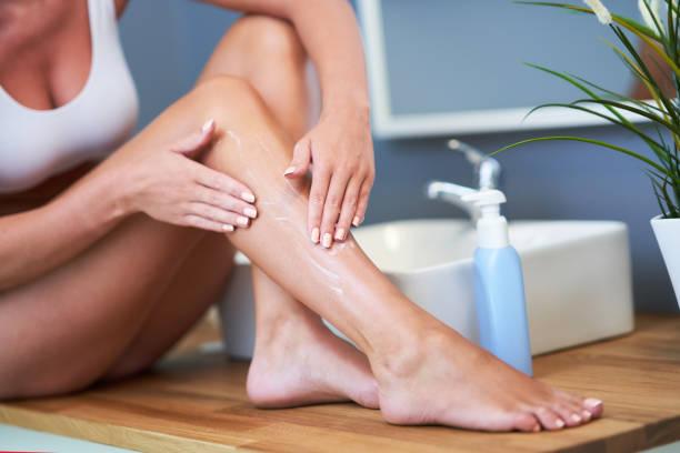 Schöne Frau Anwendung Balsam auf Beine im Badezimmer – Foto