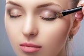 メイクアップブラシを使用して茶色のアイシャドウを適用する美しい女性。青い目のためのメイクアップ